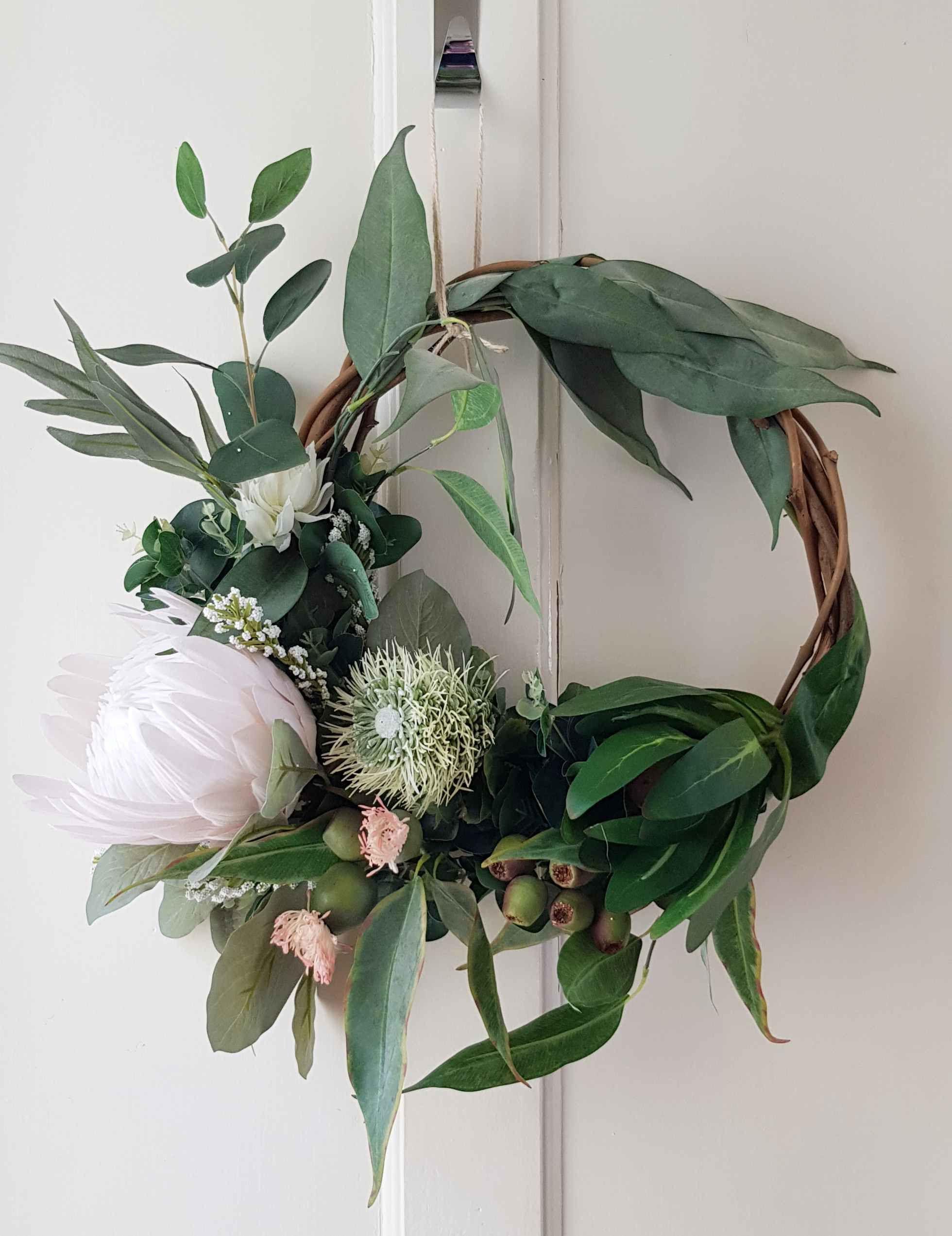 Photo of Australian native flower wreath. Wine wreath base. Door, wall decoration. Protea, eucalyptus, gumnuts, indigenous flower wreath