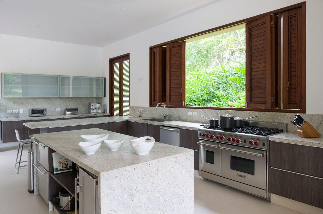 Equipada de manera profesional, la cocina, de mármol y madera oscura