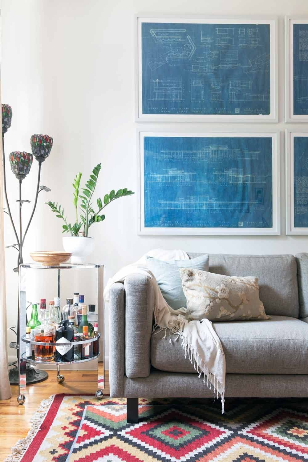 Decorate with what you have 9 things you may already own that architectural blueprints as wall art above couch and side table with plant malvernweather Choice Image