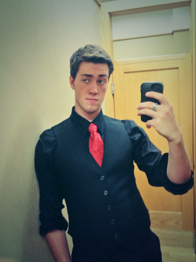 black shirt and vest with a red tie black and red best