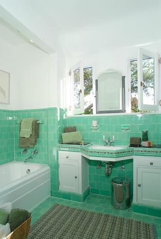 this vintage bathroom has the prettiest color green tile and other accoutrements of the era