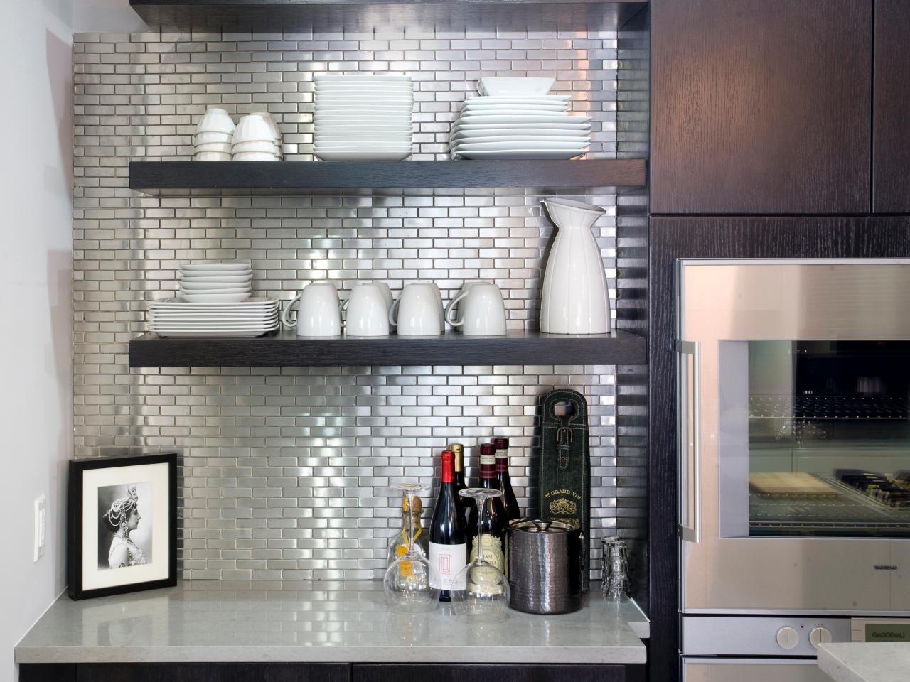 The glitzy glamour of this stainless steel backsplash belies its