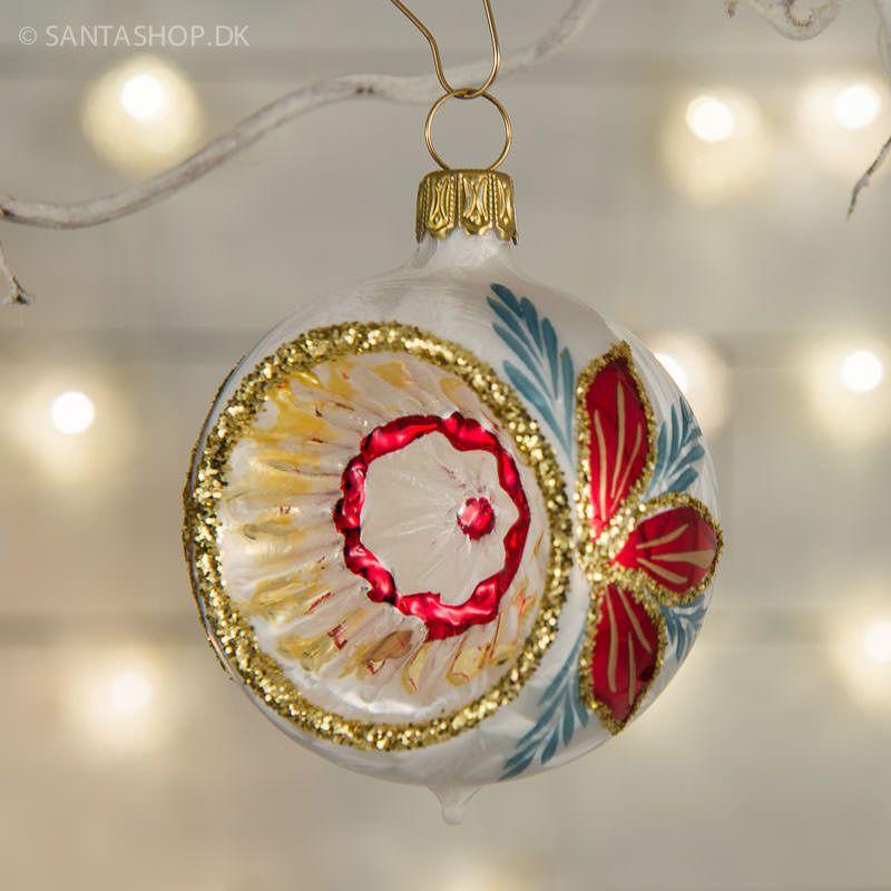 Helt unik i sit mønster og design er denne mundblæste glasreflektor. Ydersiden er designet i et mat hvid mønster der i toppen ligner fuglefjer og længere nede isblomster. Diameter 7 cm incl. kraven i guld. Reflektoren er lavet i mundblæst glas hos et meget gammelt tysk familiefirma, der er kendt for deres udsøgte kvalitet og store erfaring i gammeldags håndlavet julepynt.