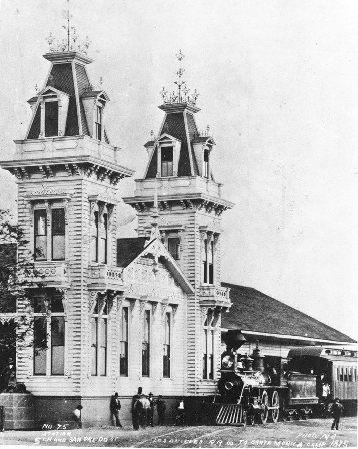 View of a steam locomotive in front of the Los Angeles and Independence Rail Road Terminal at Fifth Street and San Pedro Street, 1875. Two lavishly decorated brick towers extend from the main building to either side of its entrance.