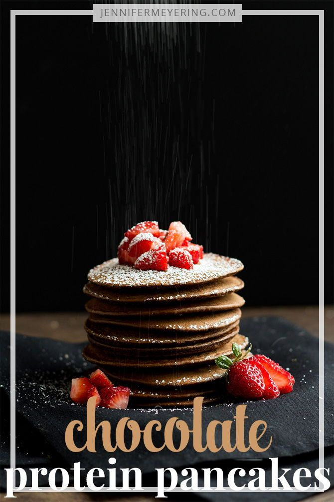 Chocolate Protein Pancakes - Start your day with a generous serving of protein pancakes made with chocolate protein powder and old fashioned oats, then top with a few strawberries and powdered sugar! #proteinpowderpancakes