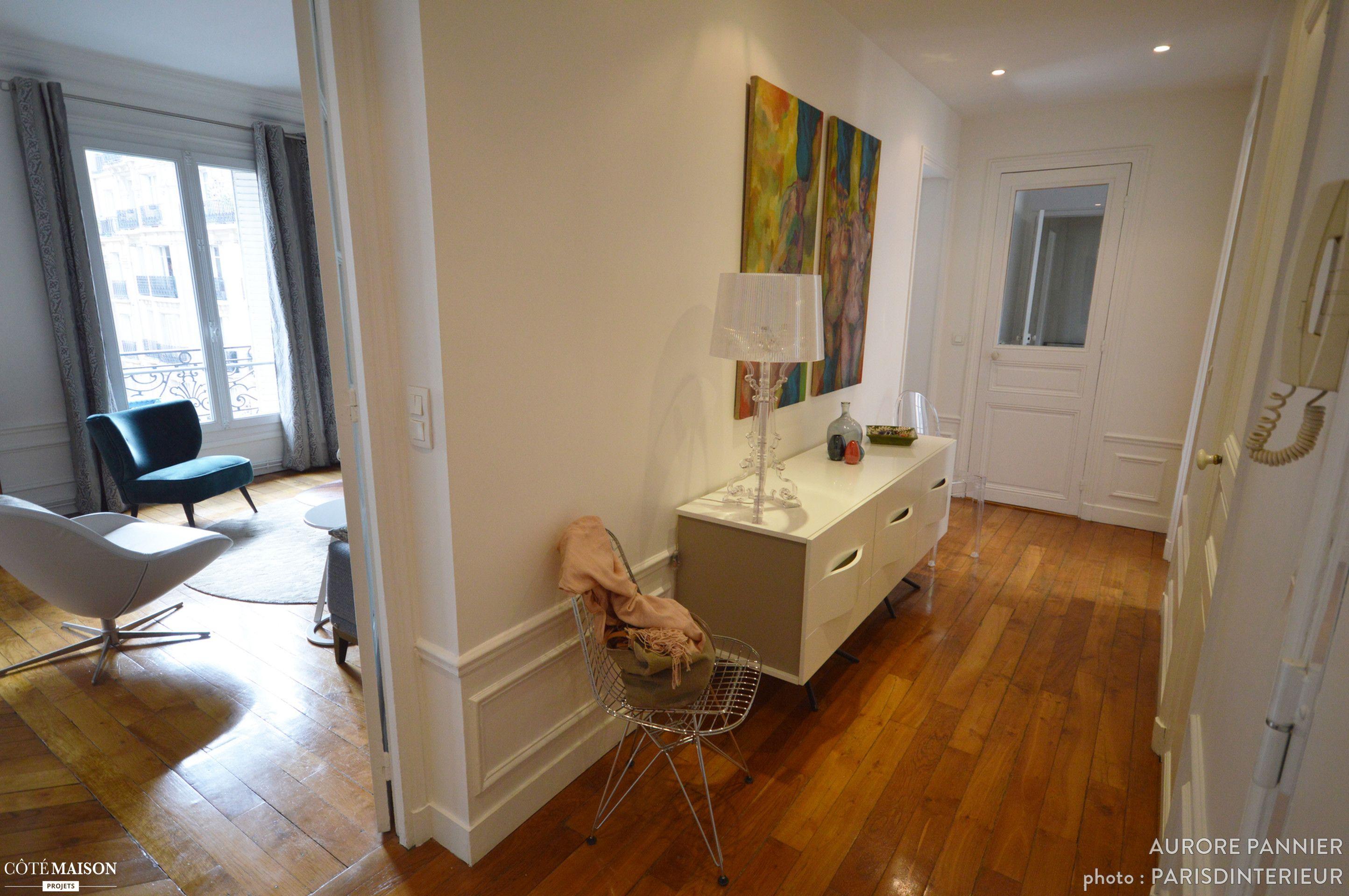 Un long couloir bien aménagé avec commode dans un appartement ...