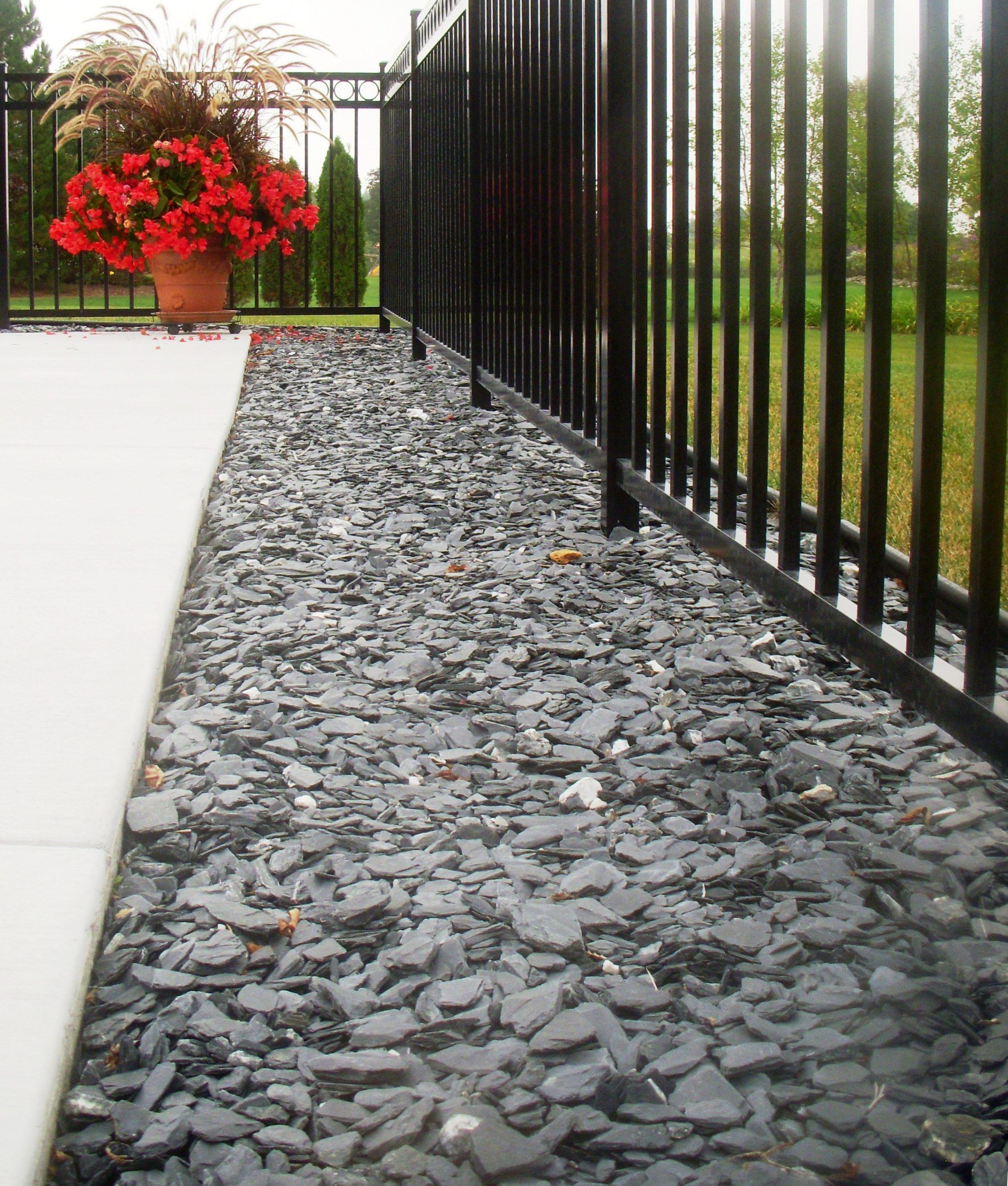 blue slate chips under a fence and along concrete is decorative