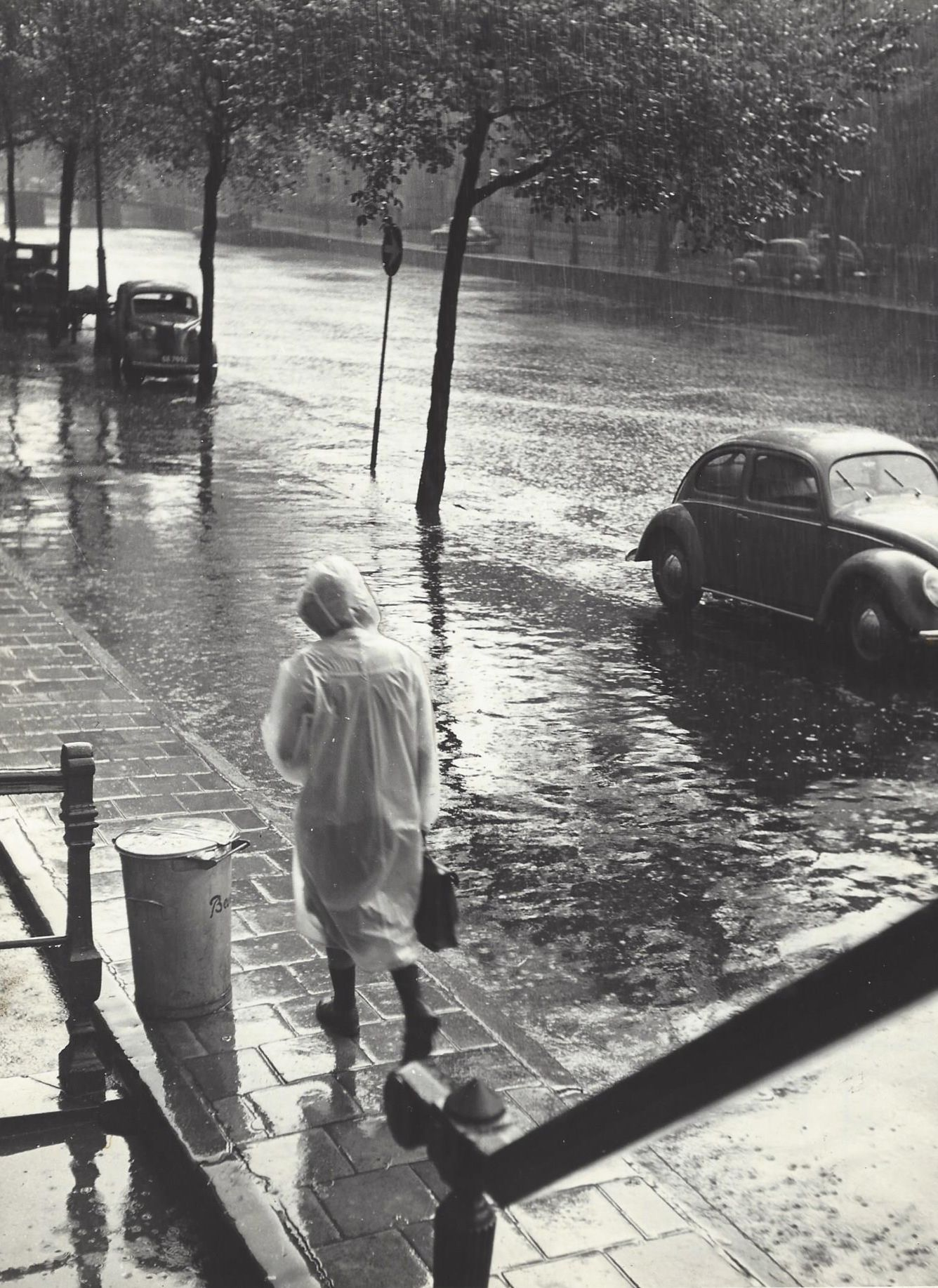 1952 - 1956. Woman walking in the pooring rain along a canal in Amsterdam. Photo Kees Scherer. #amsterdam #1952