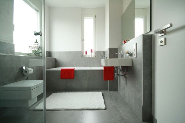 badezimmer-gestaltung-graue-fliesen-matt-rote-handtucher-akzent - badezimmer mit grauen fliesen