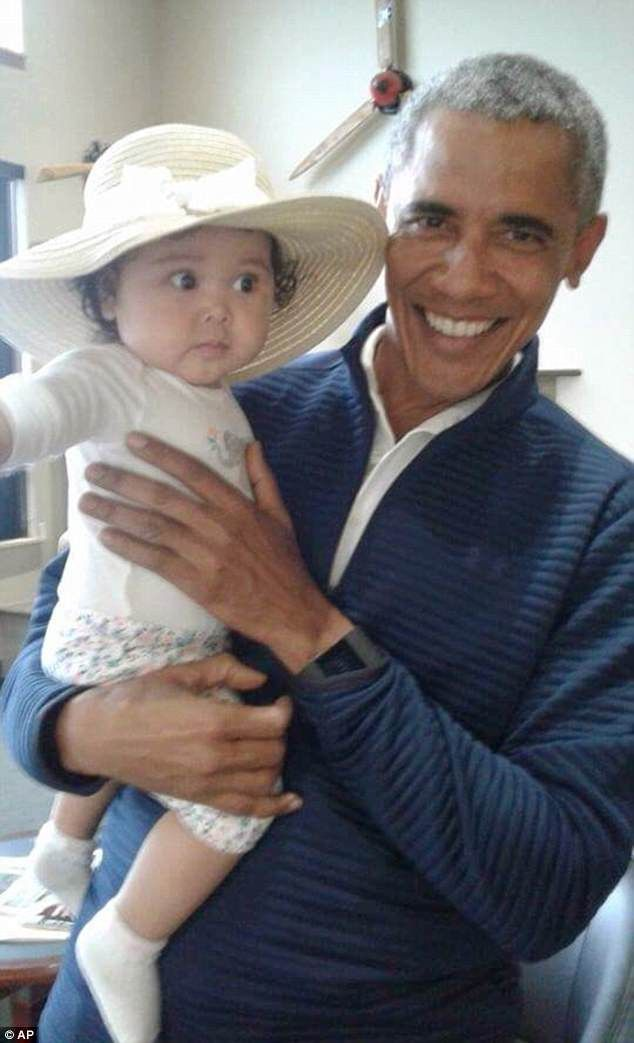 Little baby Giselle looked rather surprised to be in Obama's arms at first