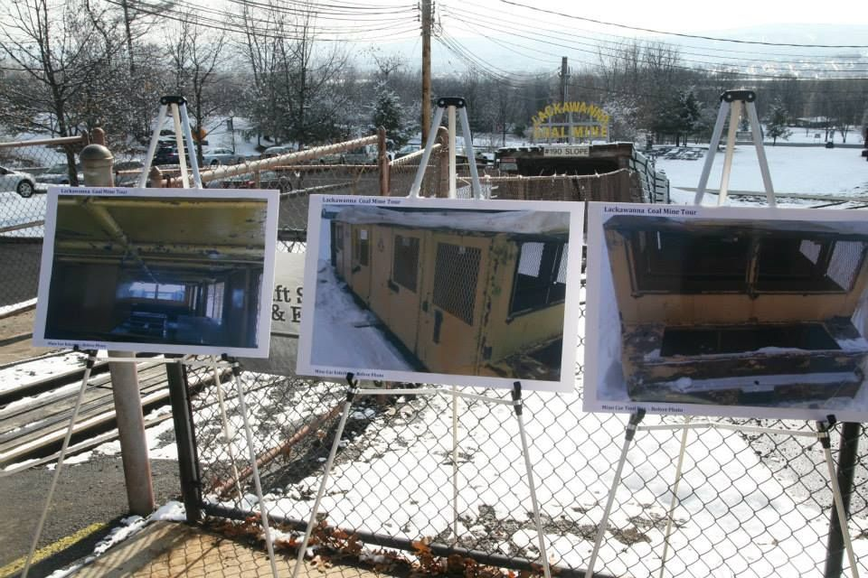 Photos of the pre-restoration passenger car for the Lackawanna County Coal Mine Tour are displayed at the entrance to the coal mine.
