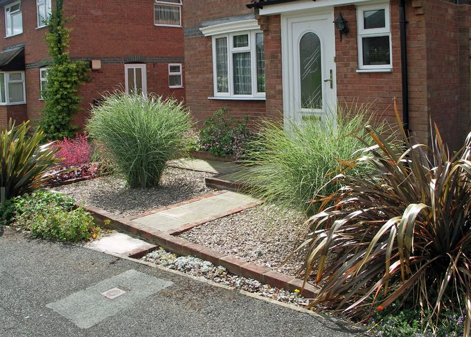 Two fine Miscanthus grasses flank the entrance path ...