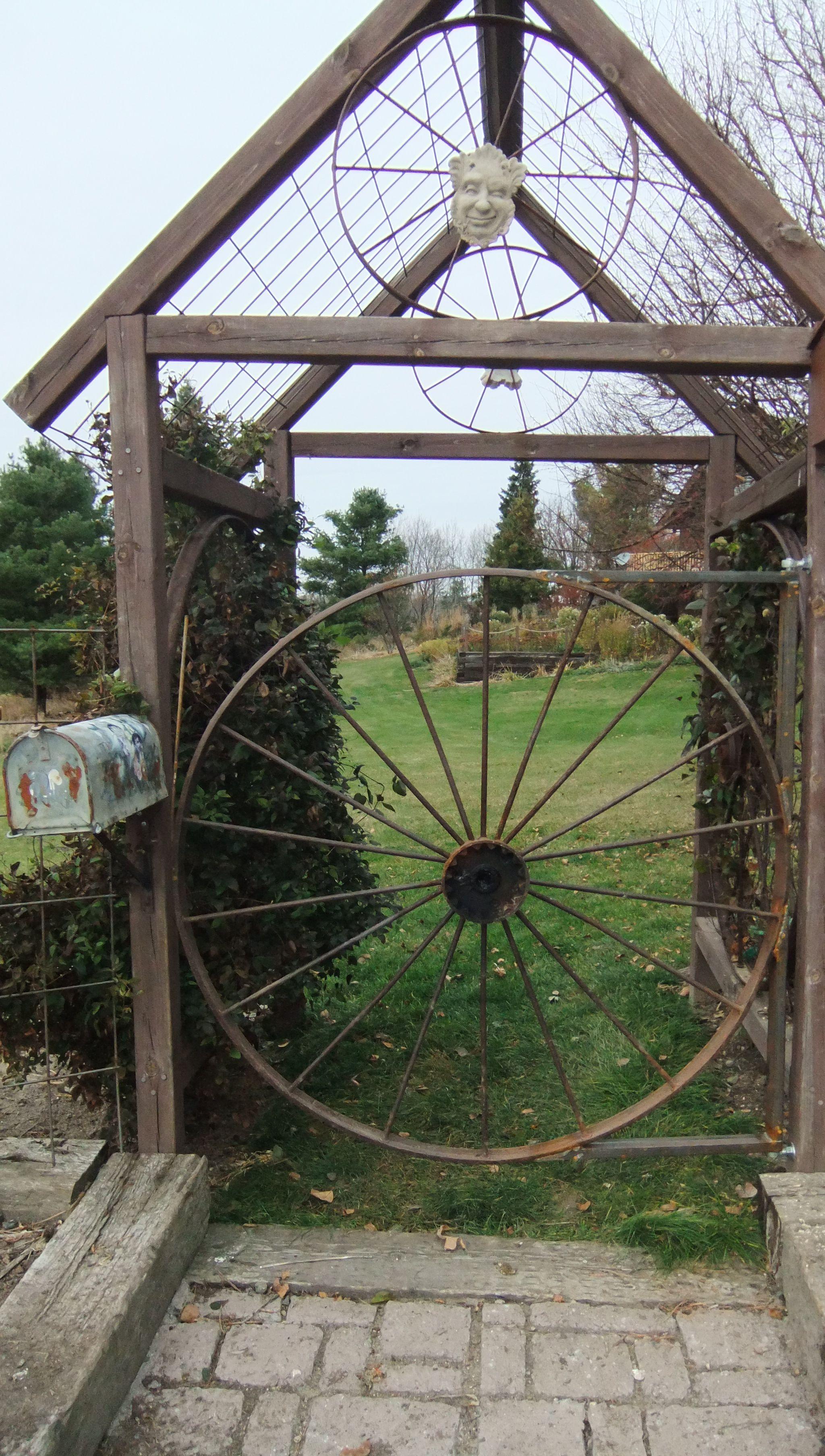 Old hay rake wheel repurposed as a garden gate outdoors for Garden fence features