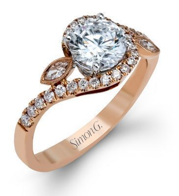 This Stylish Simon G. Engagement Ring comes to us from the Rose Collection. It is set in 18 karat rose gold and features a total weight of .28 carats of round white diamonds and .07 carats of marquise cut white diamonds.
