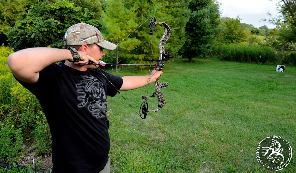 A WOMAN BOW HUNTER WITH CAMOUFLAGE MASK HUNTING WHITE TAIL