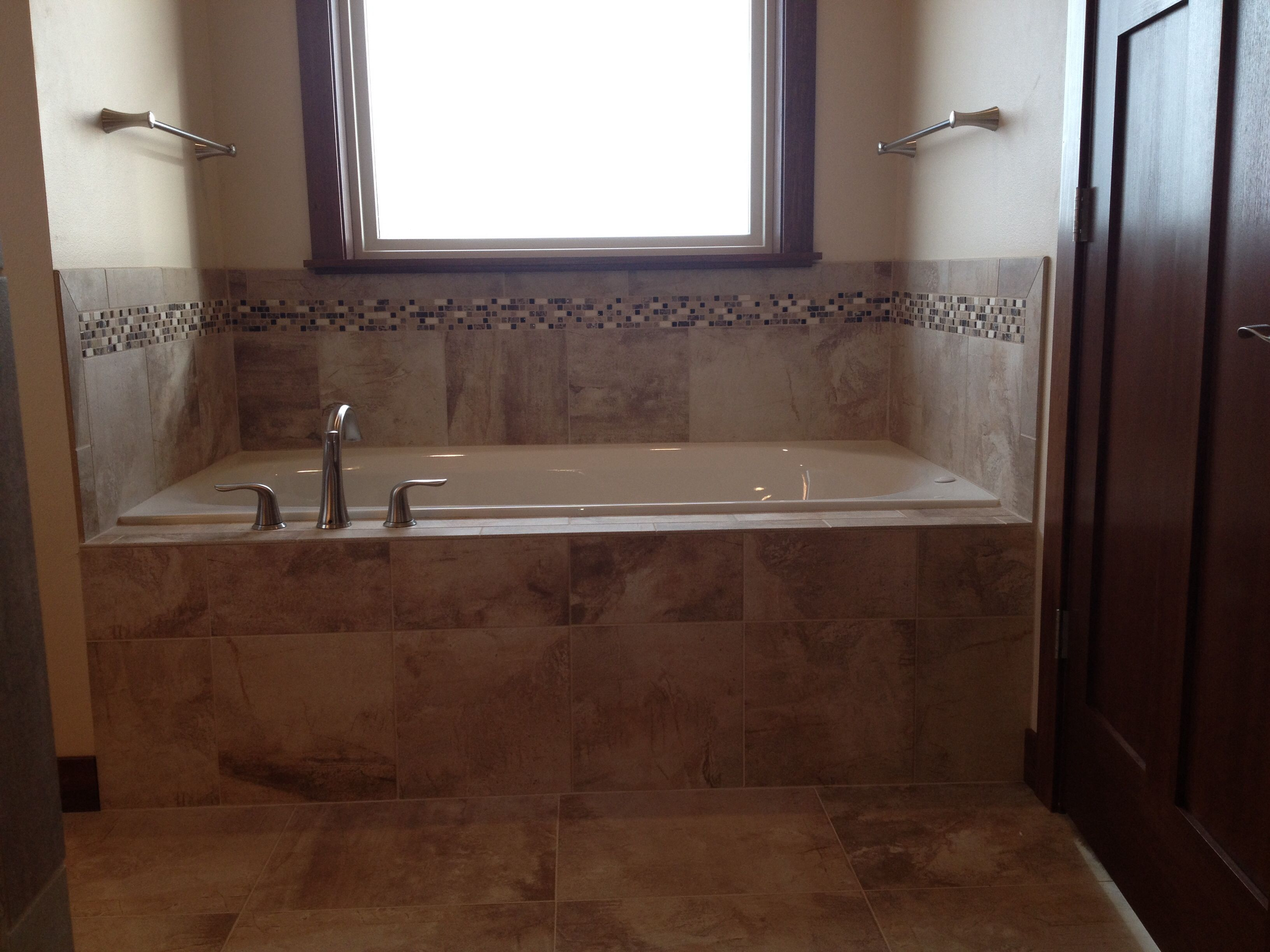 Tiled tub front and decking with mosaic trim | Design by Dennis ...