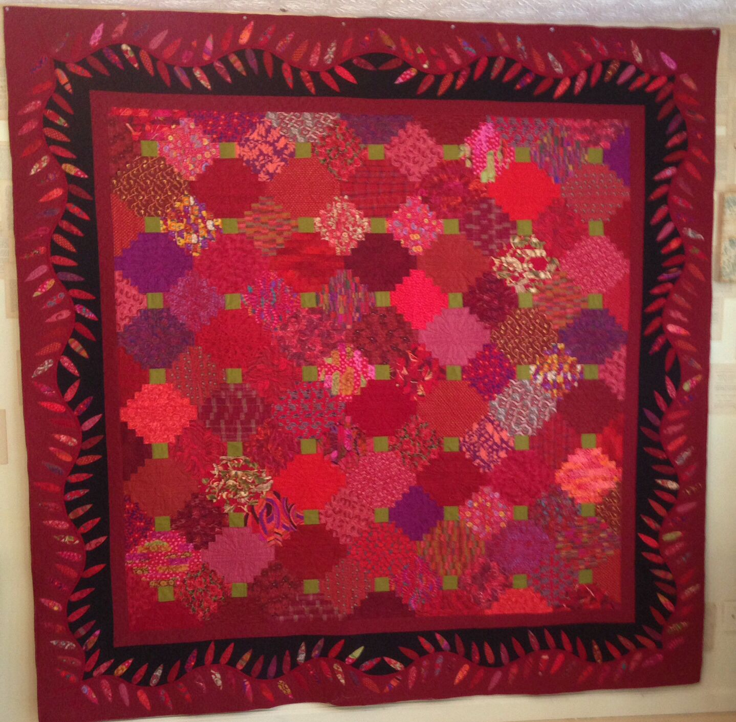 Red, She Said. A Courthouse Steps quilt with pretty border. Made for the Kaffe Fassett birthday challenge at Intown Quilters quilt shop.