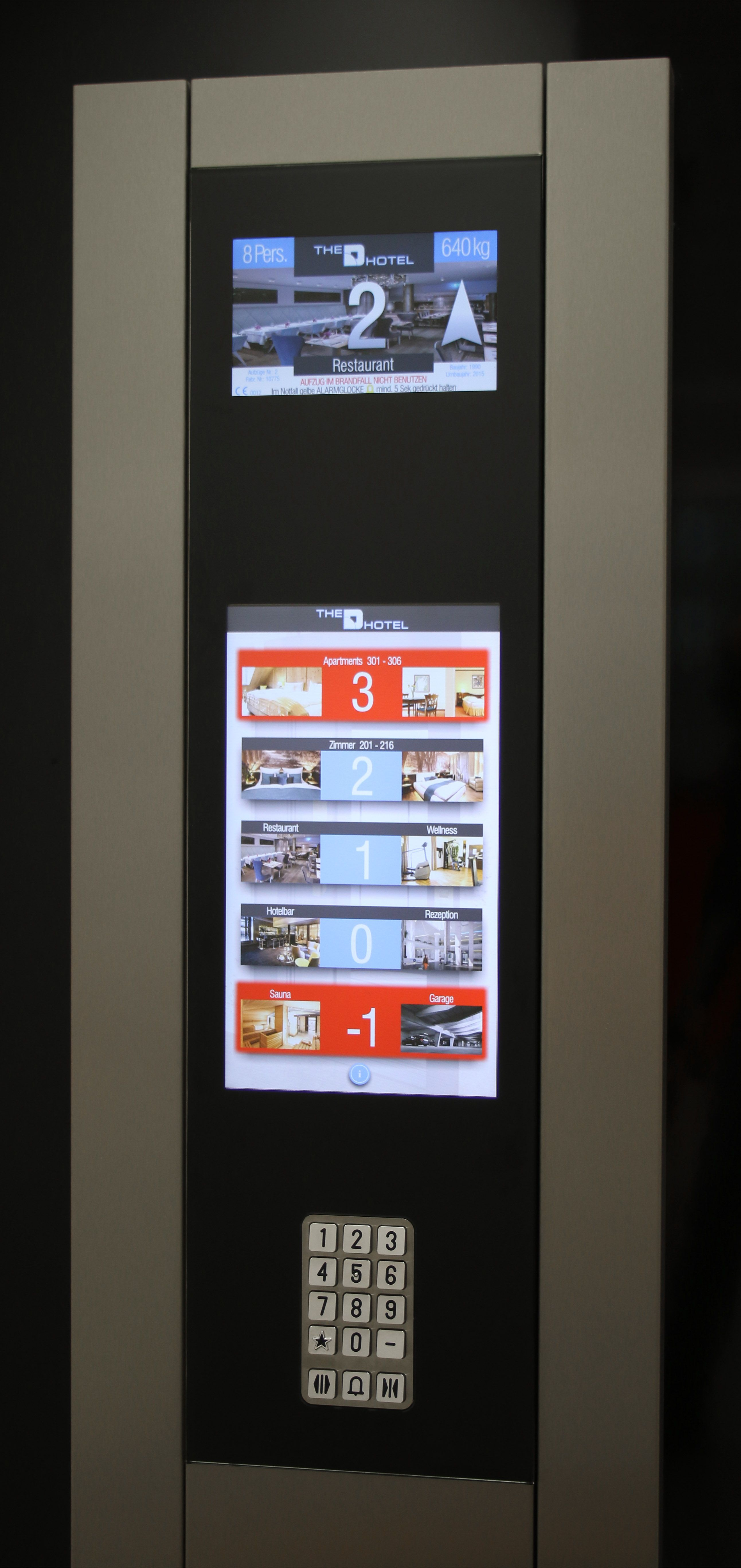 "Black tempered glass panel applied to a st/steel full-height column.  Behind the hi-resistance glass, the Matisse 10"" multimedia display and the 18,5"" Matisse Touch panel. The metal keypad on the bottom of the panel makes the full installation compliant to EN81-70 code."