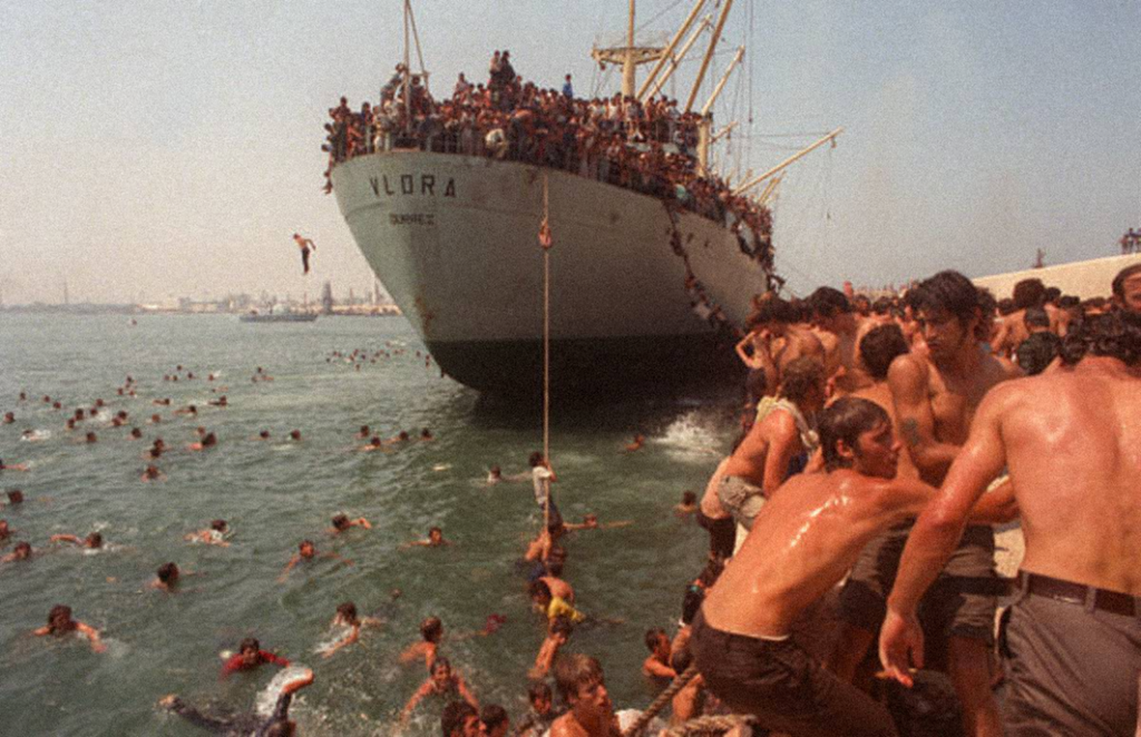 """""""On 8 August 1991, several ships carrying approximately 15,000 Albanian migrants succeeded in entering the port of Bari, Italy. The Italian government's response was harsh. Most of the Albanians were detained in a sports stadium without adequate food, water, or access to bathrooms. Italian authorities dropped supplies to the detained migrants by helicopter. Within several weeks most of the migrants were deported to Albania."""""""