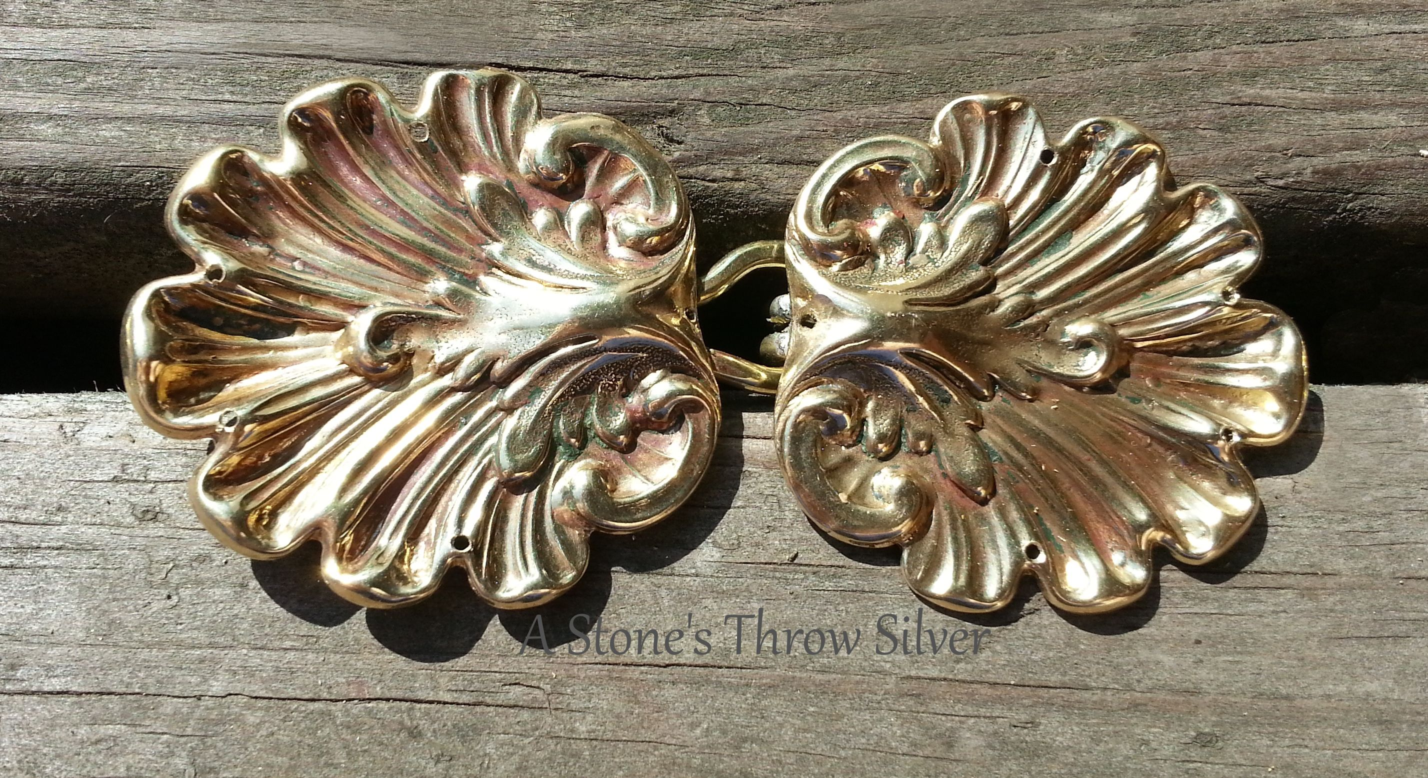 Shell and Acanthus Cloak Clasps, $35. These shell-shaped medium weight clasps are solid brass, have five stitching holes on each shell, and have acanthus leaf accents. Designed to be a secure closure for every day wear, LARPing, Highland games, Renaissance events, rituals, or any other place that you would wear your favorite cloak.