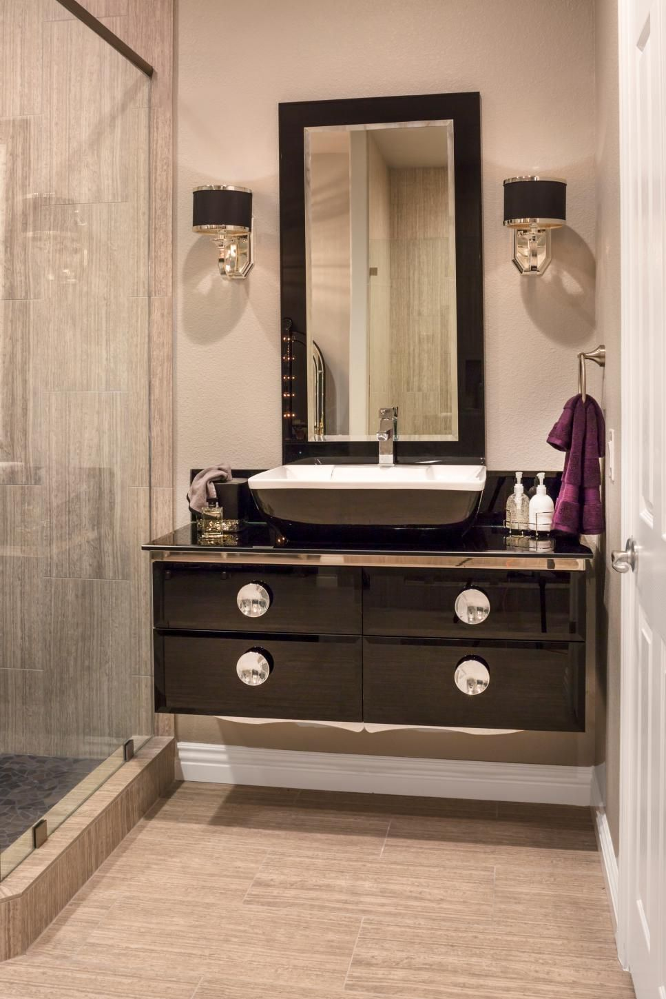 Sleek Modern Dark Bathroom With Glossy Tiled Walls: A Glossy Black Floating Nightstand Is Topped With A Sleek