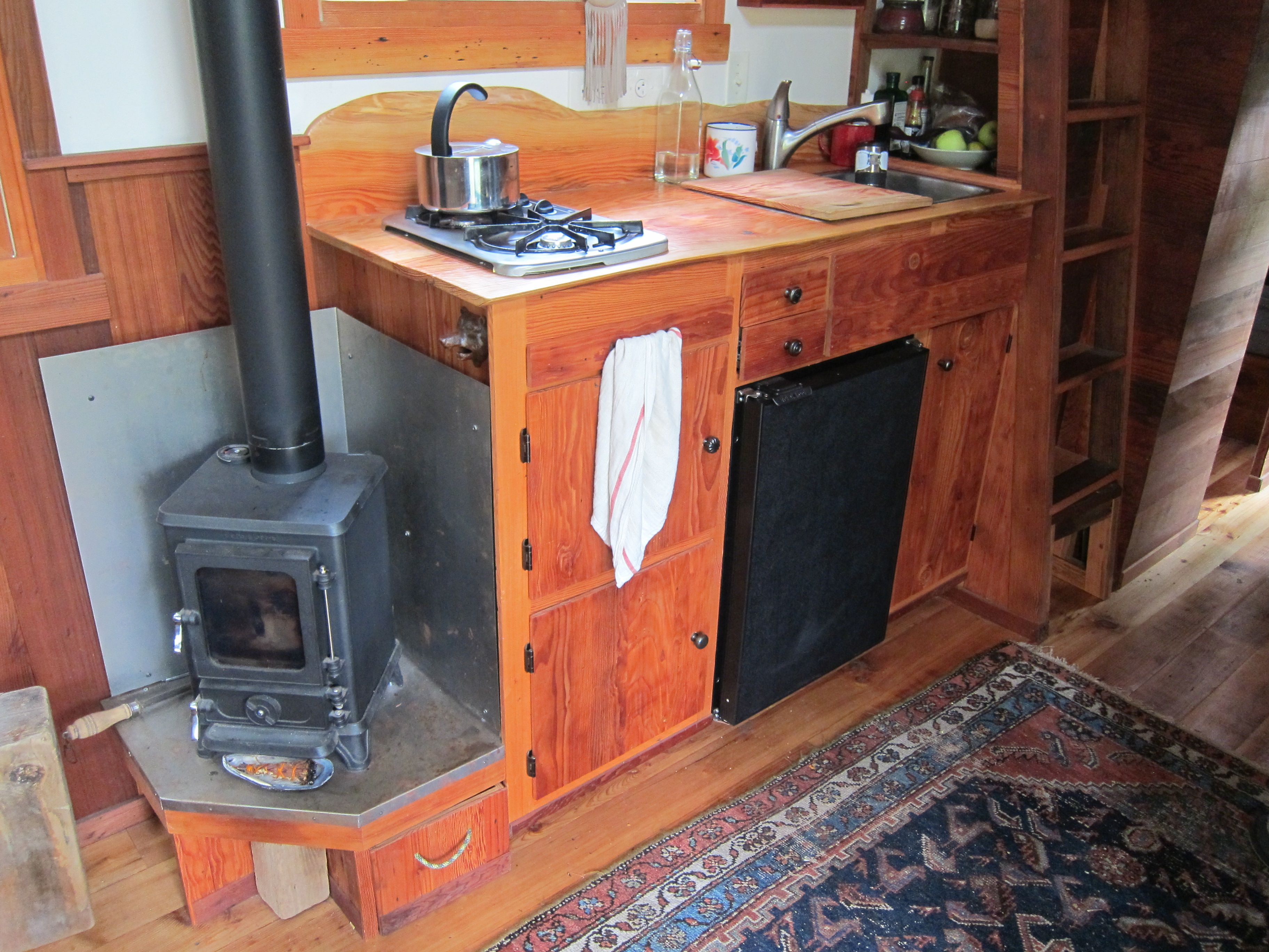 This adorable tiny woodstove is next to a gorgeous custom door