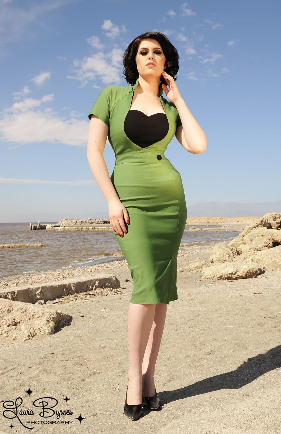 Veronica Dress in Green with Black Heart  - The Veronica is an hourglass girls dream in curve-loving bengaline with a nipped-in waistband and an adorable heart-shaped frame at the bust.  Lots of stretch everywhere but the waist, this sexy wiggle will accommodate a range of bust and hip sizes.  Finished off with a charming decorative button detail, front slit, and back zipper.