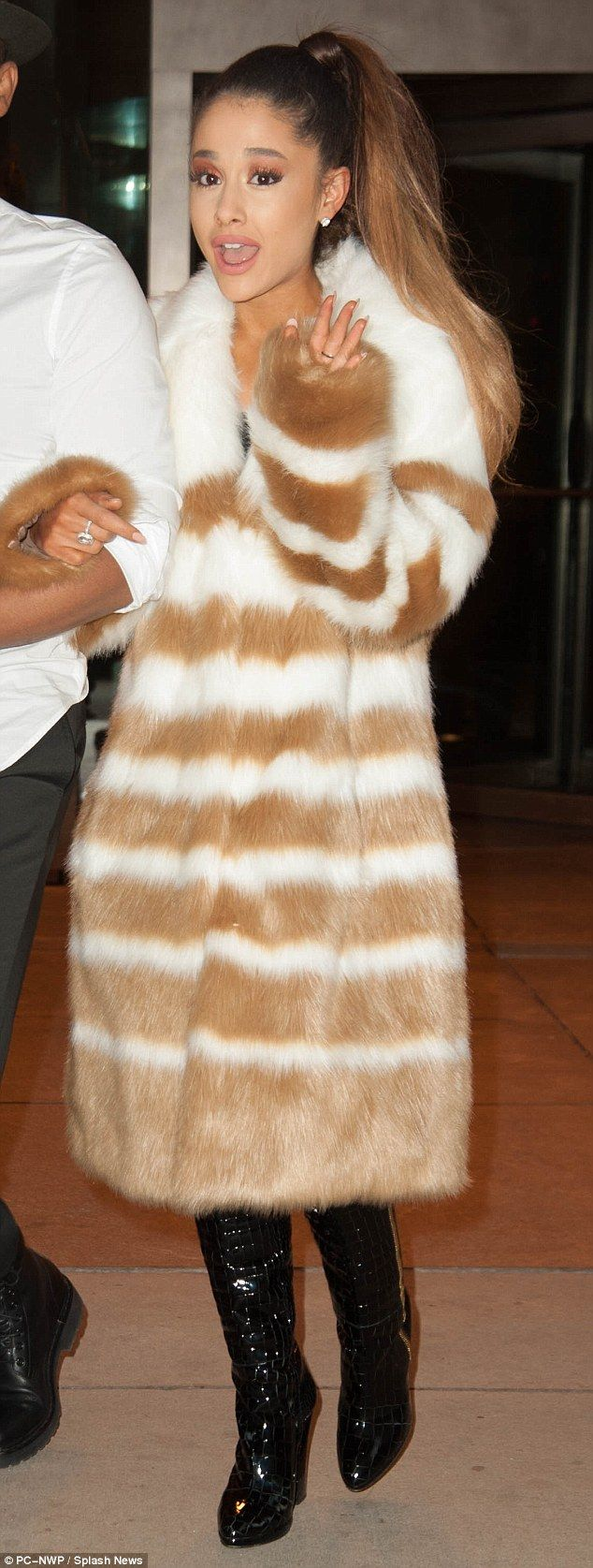 3155cdd1fa Unusually skin shy: Ariana Grande was completely covered up as she stepped  out in NYC on Wednesday in a faux fur coat and knee-high shiny black boots