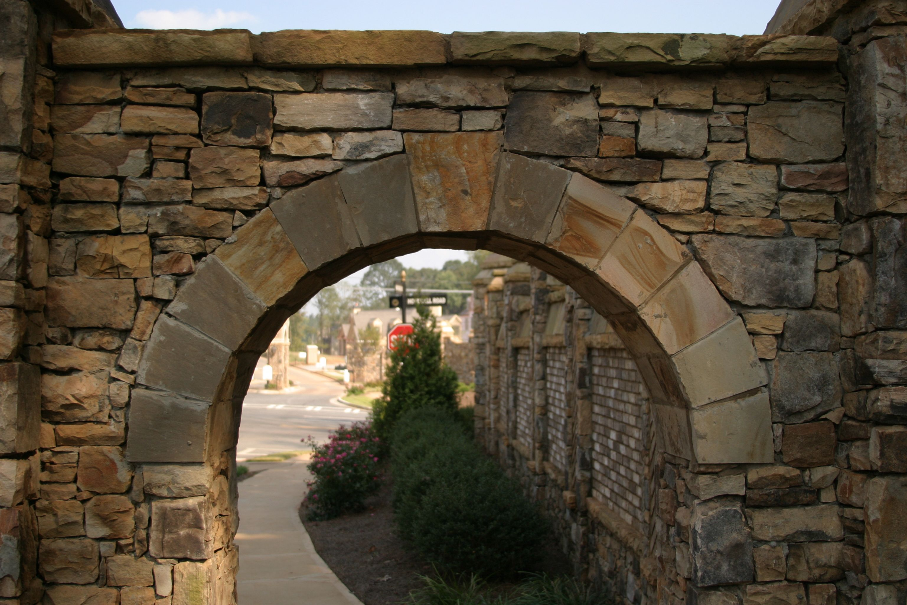 Keystone Natural Stone Archway Leading To A Garden Walkway Or