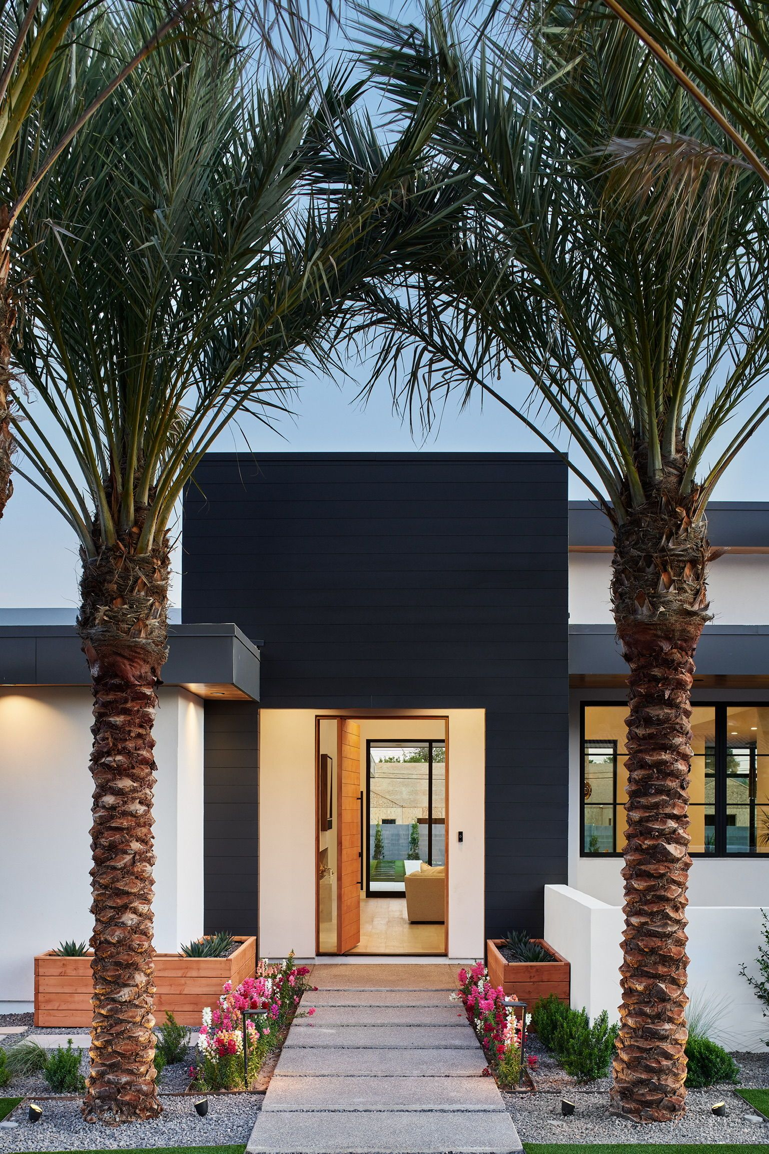 Palm tree lined entryway to this beautiful modern home with clean black and white exterior. Oversized front pivot door and clean landscaping. This is the modern home of our dreams! Find in Arcadia, AZ. #exteriordesign #curbappeal #modernlandscaping