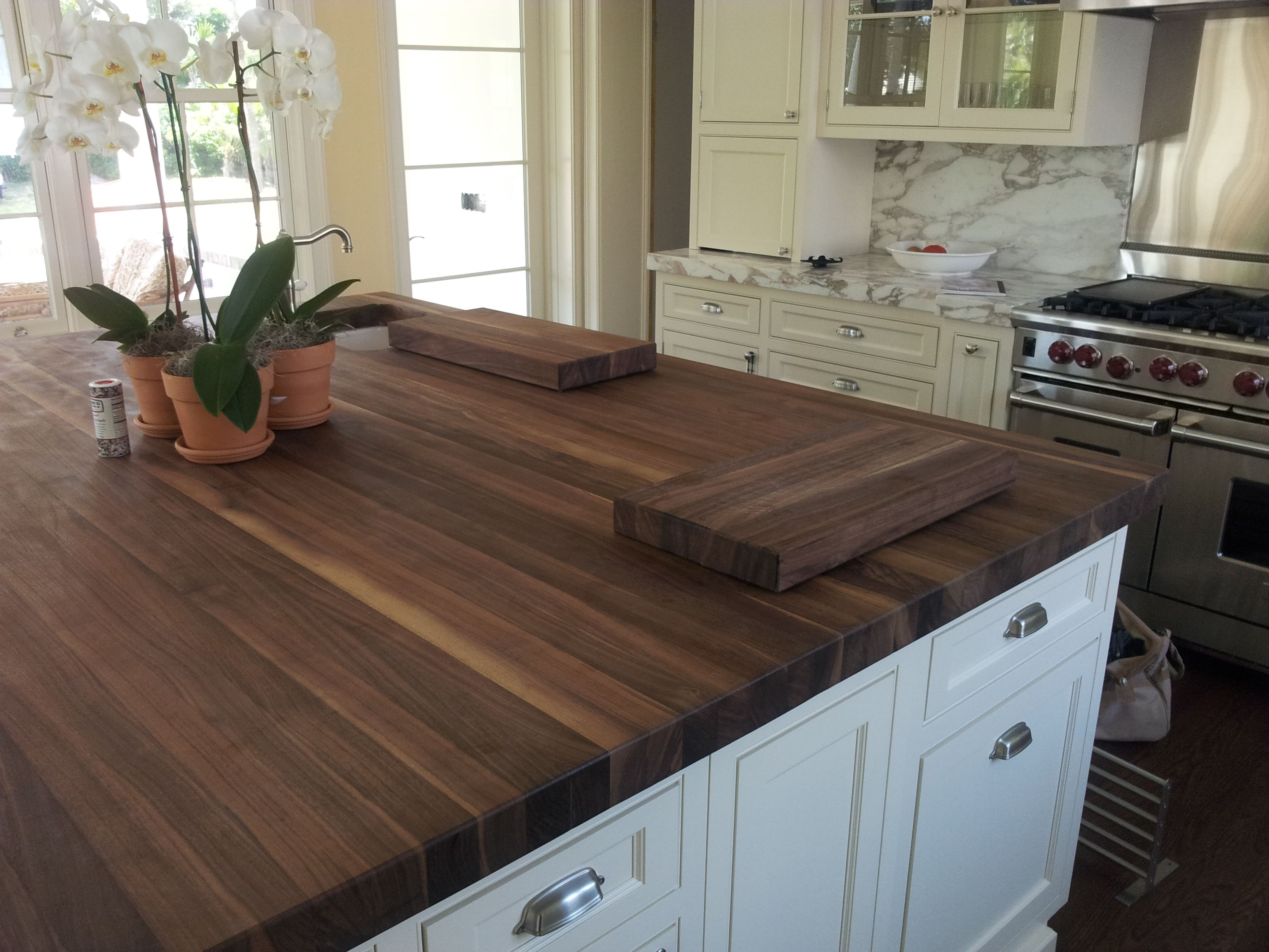 Dark Butcher Block Countertop With White Cabinets And Stainless