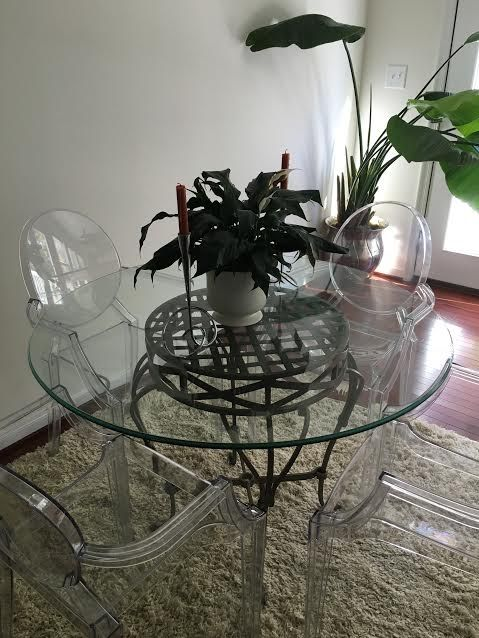 Great for breakfast nook, this table has wrought iron base and is paired with clear acrylic chairs for a modern look