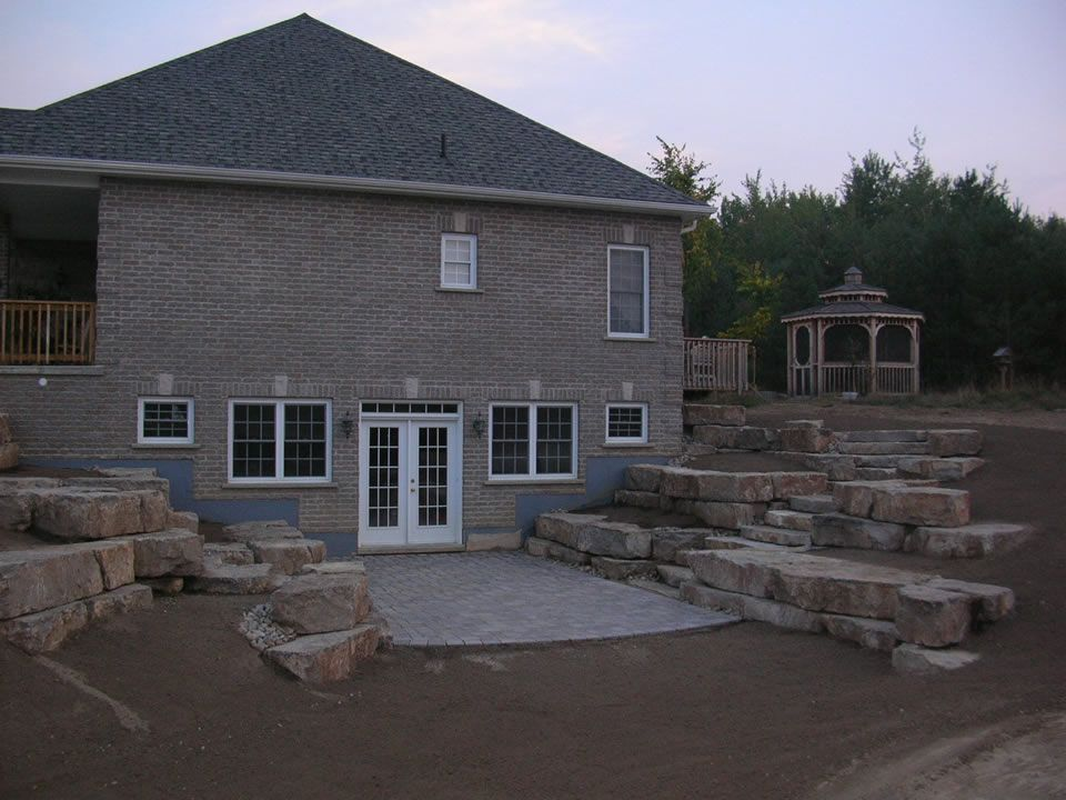 Walkout basement with limestone tiered retaining walls for Walk in basement