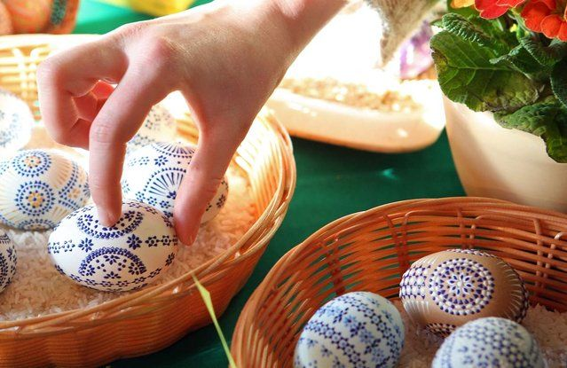 A visitor selects a decorated Easter egg at the annual Easter egg market on March 16, 2013 in Schleife, Germany. Easter is a particularly important time of year for Sorbs, a Slavic minority in eastern Germany, and the period includes the tradition of painting Easter eggs that include visual elements intended to ward off evil. Many Sorbs still speak Sorbian, a language closely related to Polish and Czech.  (Photo by Adam Berry)