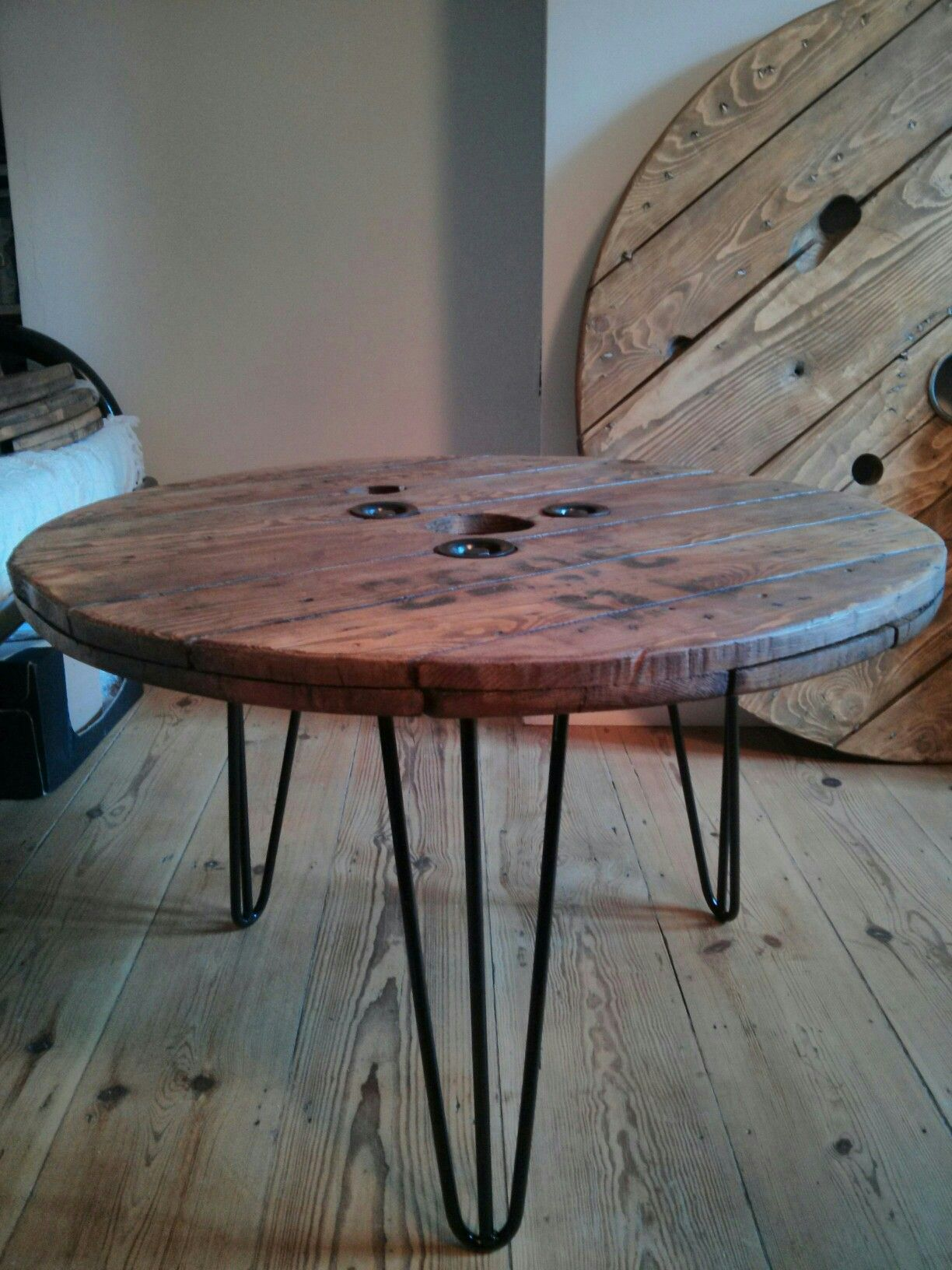 Upcycled electric cable reel now coffee table with hairpin legs