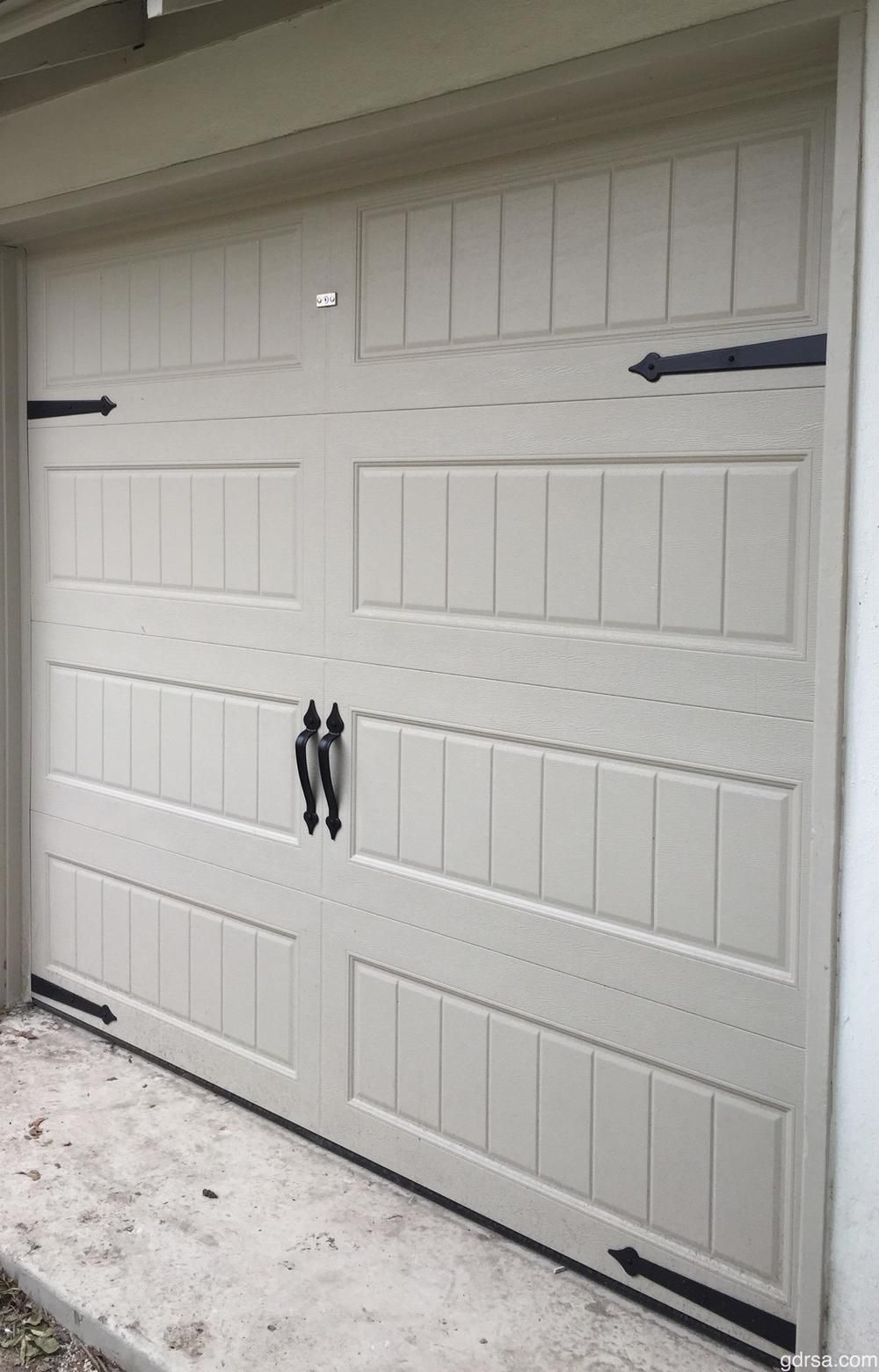 A Light Gray Steel Garage Door With Short Panel Pattern Also Uses Magnetic Hardware For Additional Style