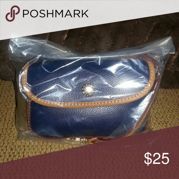 Dooney & Bourke This is a navy blue wristlet with brown trim. All leather. Pretty chevron design on the inside.  Brand new and still in the bag. Dooney & Bourke Bags Clutches & Wristlets