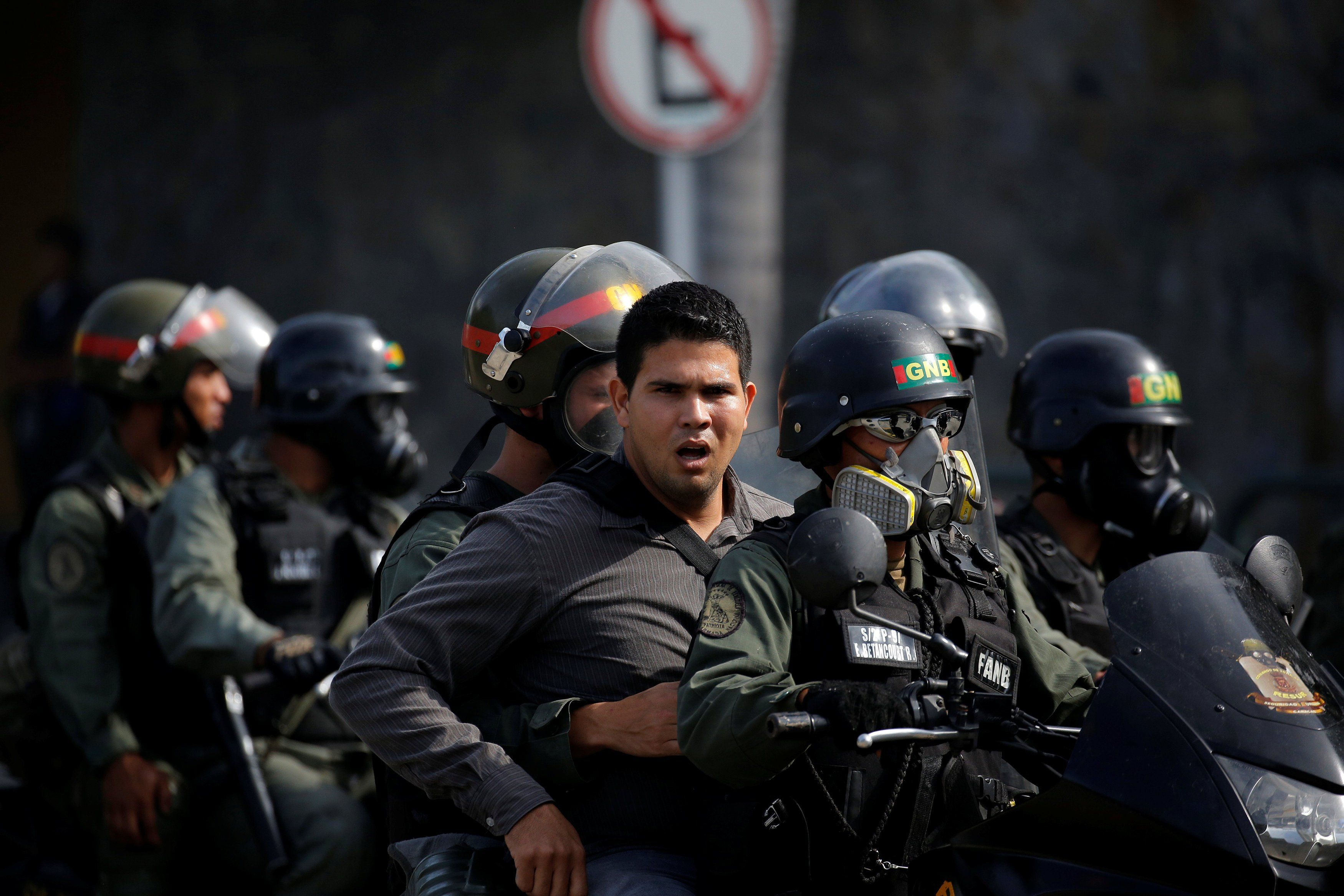 Riot security forces escort an unidentified man during a rally against President Nicolas Maduro in Caracas, Venezuela, May 24, 2017. REUTERS/Carlos Barria