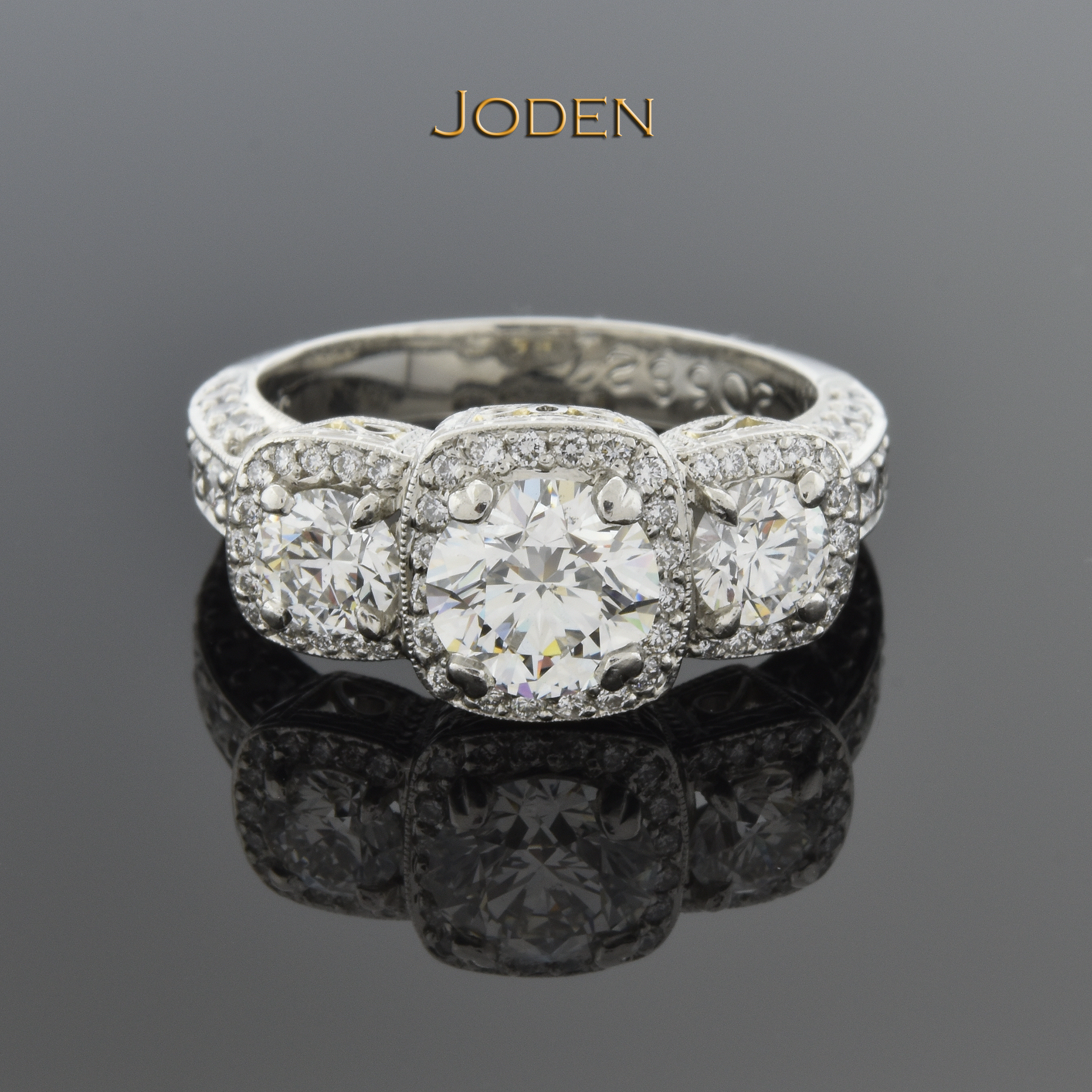 The three stone diamond ring has been invented and reinvented for nearly a century. This modern version features a diamond halo around each before blending into the diamond accents.  The center holds one round brilliant cut diamond that has a weight of 1.05 carat. Two round brilliant cut diamonds that have a weight of .60 carat total weight. This ring is accented by 76 round brilliant cut diamonds that have a weight of .74 carat total weight.