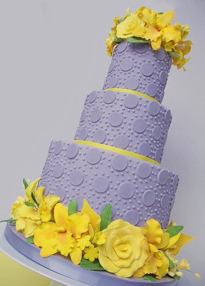 blue/gray and bright yellow tiered cake ... luv the textures on the smooth blue layers ... dimensional roses and lilies on top and ringing the base .... lovely!!
