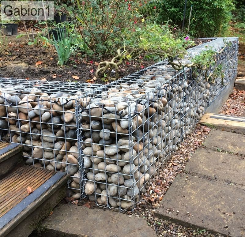 small garden gabion retaining wall filled with rounded cobbles