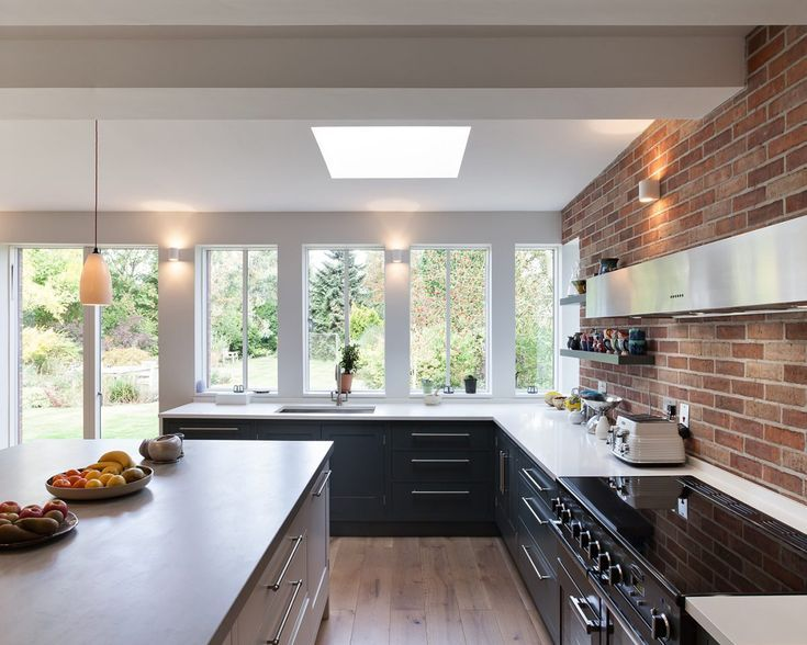 a beautiful kitchen with exposed brick wall dark blue cabinetry and large windows kitchen on kitchen interior with window id=41068