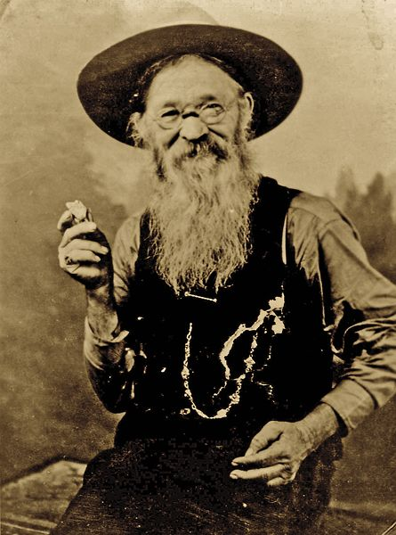 """In 1883, Potato Creek Johnny moved to Deadwood, Dakota Territory; he wouldn't discover the gold nugget he holds here until after 46 years of prospecting. He used to say the nugget looked like a woman's leg. """"'I'm still looking for the leg,' he would tell everyone,"""" Mary Kopco says.  – Courtesy Deadwood History, Adams Museum Collection, Deadwood, SD –"""