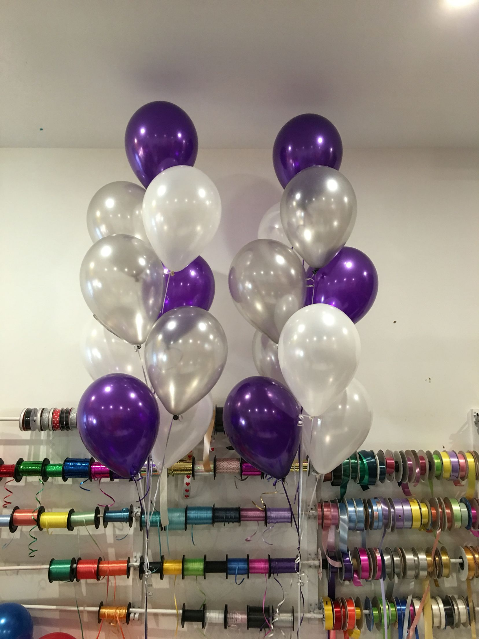 Mix of purple, silver and white latex balloons on a floor ...