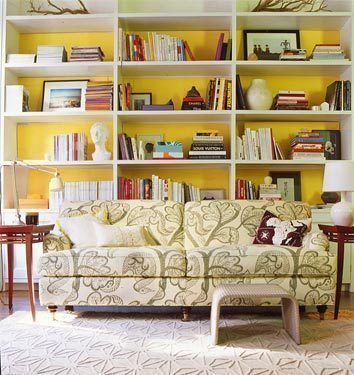 A wall of bookshelves accented with yellow paint on the interior ...