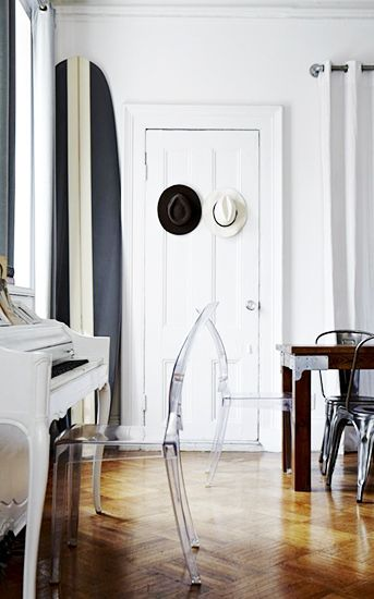 21 Homes That Prove Surf Is Chic // surfboards as decor // Louis Ghost Chair, white living room and dining room, white piano