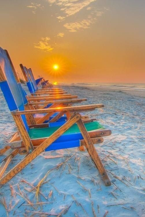 Chairs On The Sand At The Beach During Sunrise