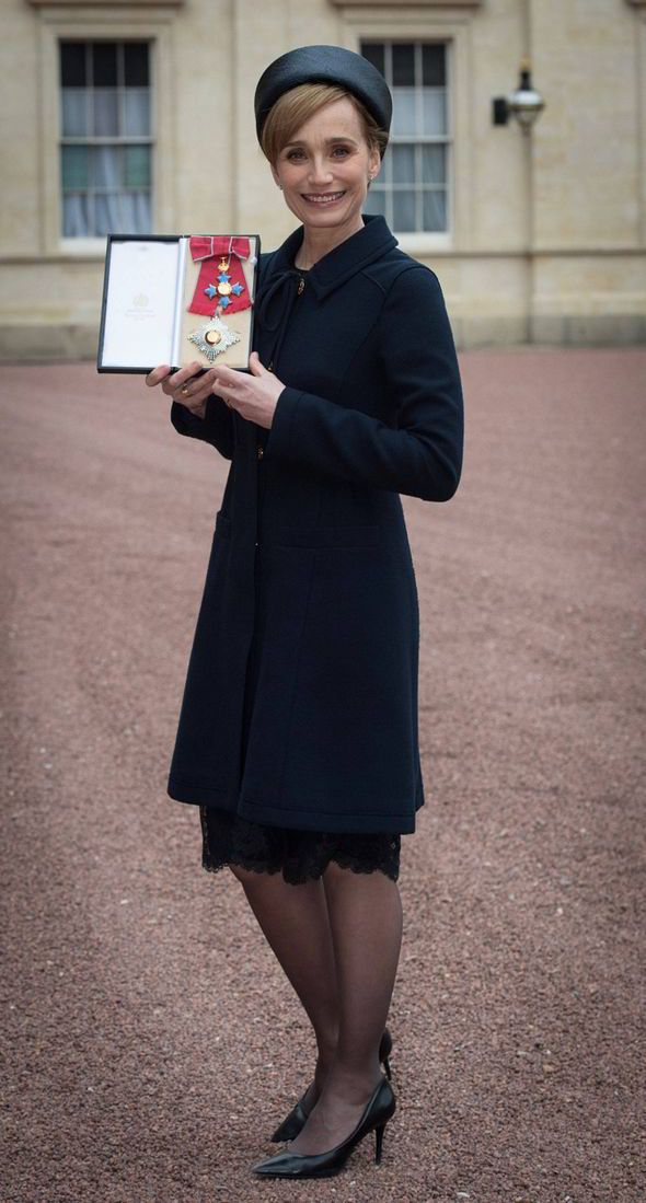 Dame Kristin Scott Thomas holding her Dame Commander of the British Empire medal presented to her by Queen Elizabeth II at Buckingham Palace on March 19, 2015 in London, England.