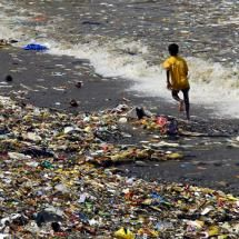A boy runs barefoot in a sea of garbage on a beach in Mumbai, India