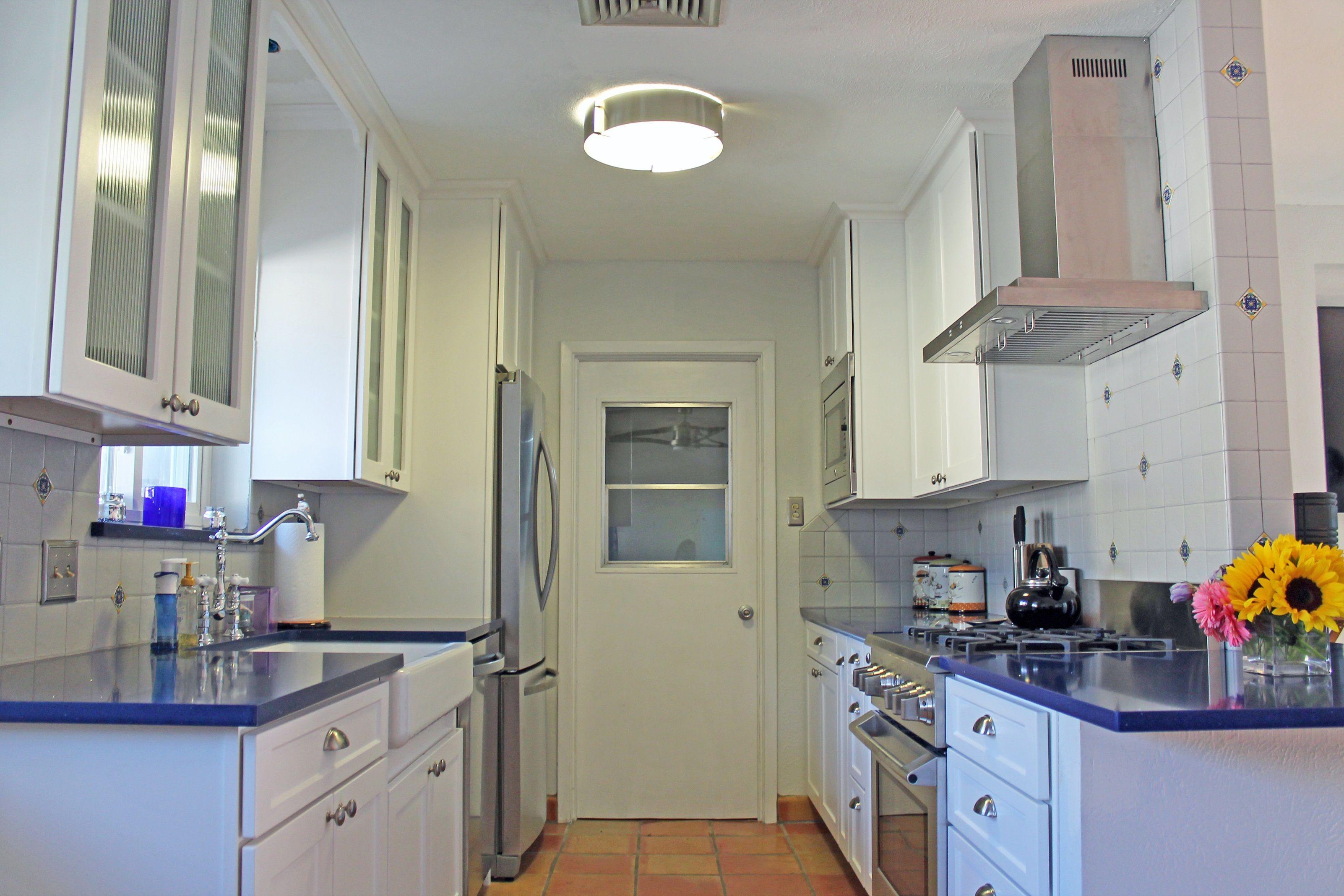 Spanish Modern Kitchen Design White Cabinets Stainless Steel Appliances And Blue Quartz Countertops Saltillo Floor Tile Home Kitchens Flooring Countertops